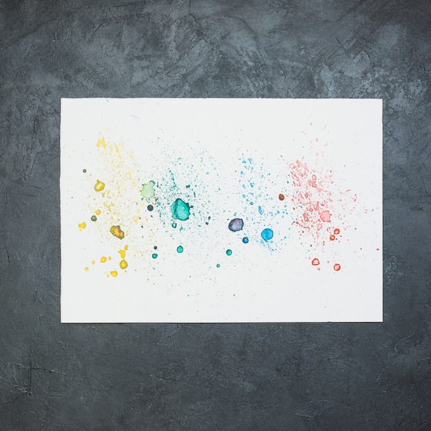 Colorful water color stain on white paper over black backdrop Free Photo