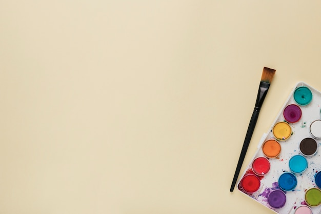 Colorful watercolor palette and paint brush on beige backdrop Free Photo