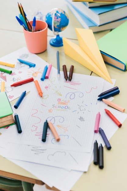 Colorful wax crayons scattered on desk with kid drawings Free Photo