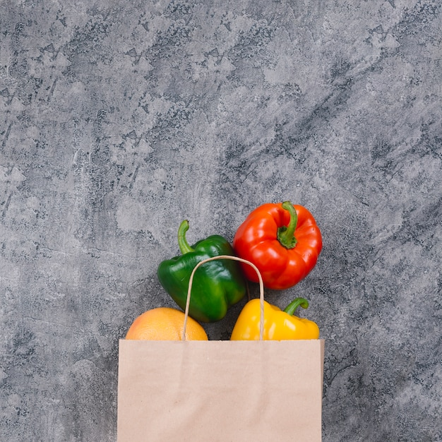 Colorful whole capsicum from the paper bag on concrete backdrop Free Photo