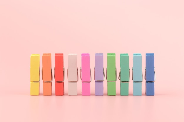 Colorful wood clothespins pegs on a pink background Premium Photo