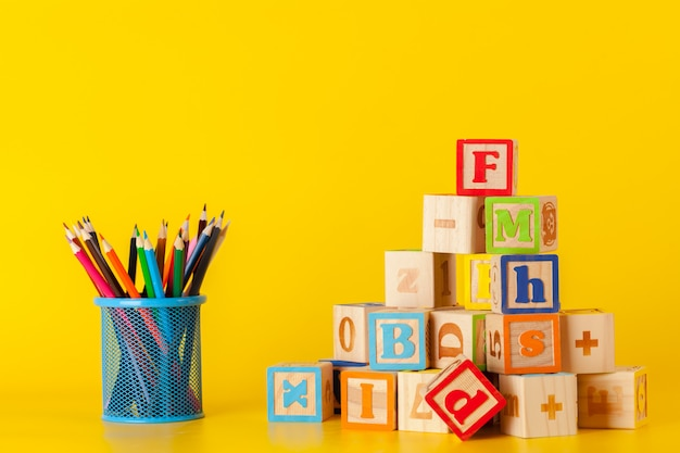 Colorful wooden blocks and cup with colorful pencils Premium Photo