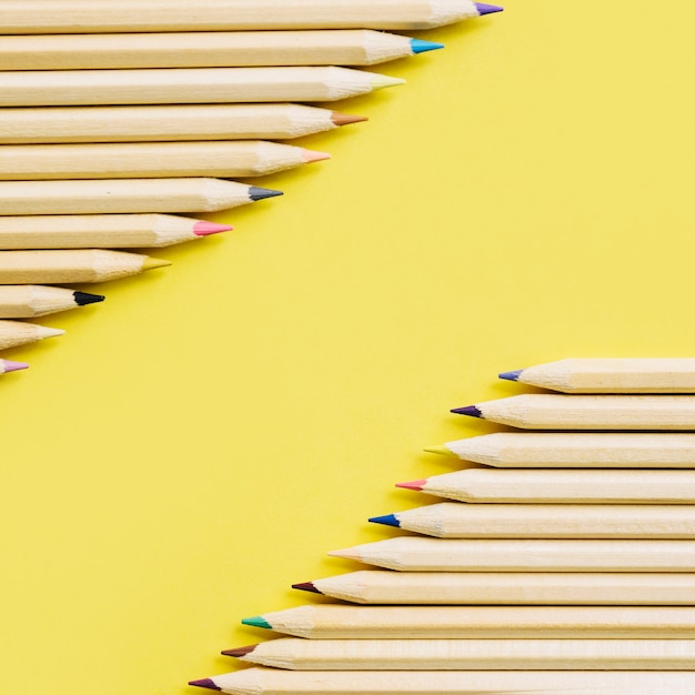 Colorful wooden pencils in a row on yellow backdrop Free Photo