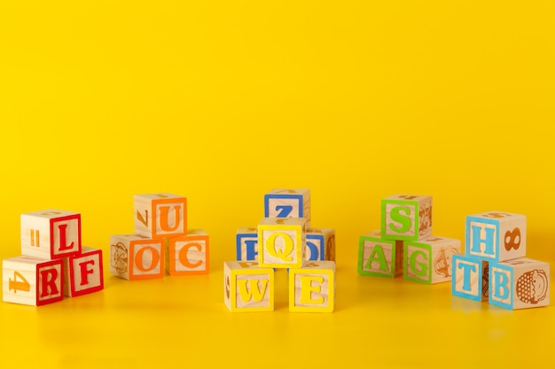 Colorful wooden surface blocks with letters on a yellow color Premium Photo