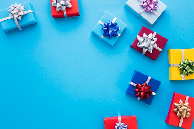Colorful wrapped gift boxes with bow on blue background Free Photo