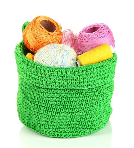 흰색 절연 녹색 바구니에 뜨개질에 대 한 다채로운 원사 프리미엄 사진