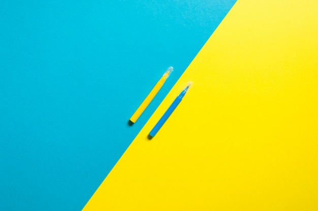 Colorful yellow and blue background with two pens Premium Photo