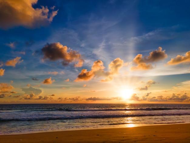 黄色、青空、太陽光線とカラフルな熱帯のビーチの夕日。タイプーケットビーチで海に沈む夕日。 Premium写真