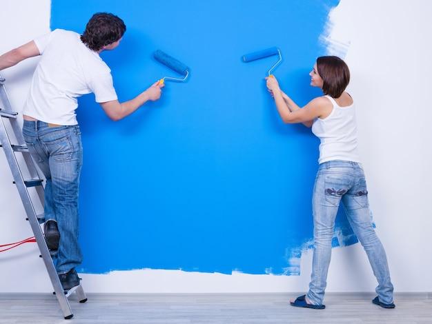 Окрашивание стены в синий цвет молодой парой в повседневной одежде Бесплатные Фотографии
