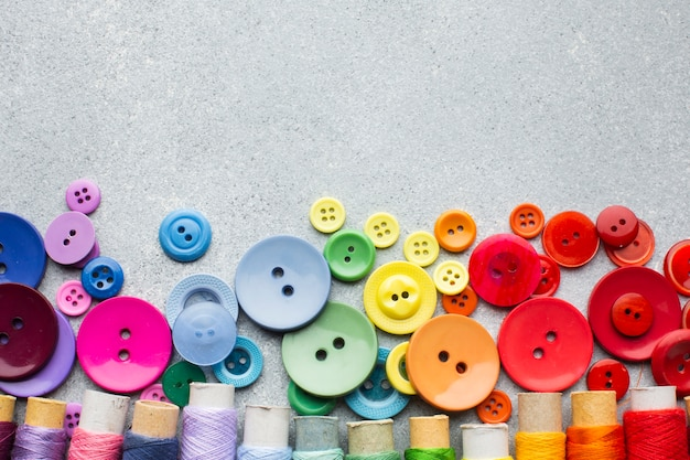 Coloured buttons and thread rolls with copy space background Free Photo