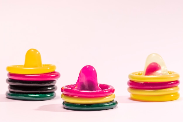 Colourful condoms on pink background Free Photo