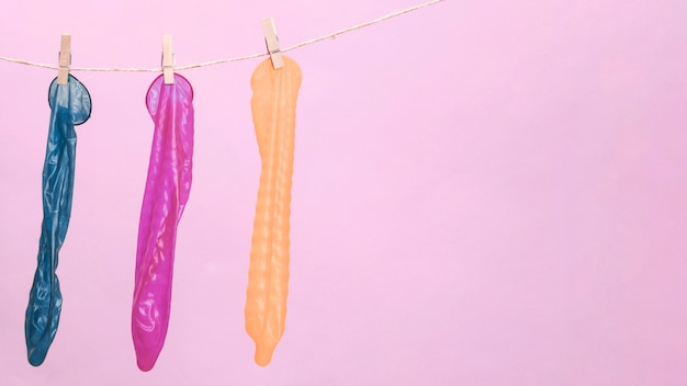 Colourful condoms with clothespin and copy-space Free Photo