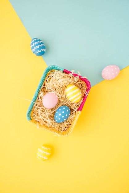 Colourful easter eggs in small basket on table Free Photo