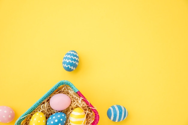 Colourful easter eggs in small basket on yellow table Free Photo