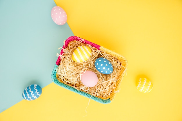 Colourful easter eggs in small basket Free Photo