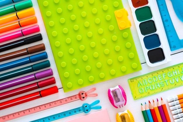 Красочная плоская доска для рисования мелом на белом столе Premium Фотографии