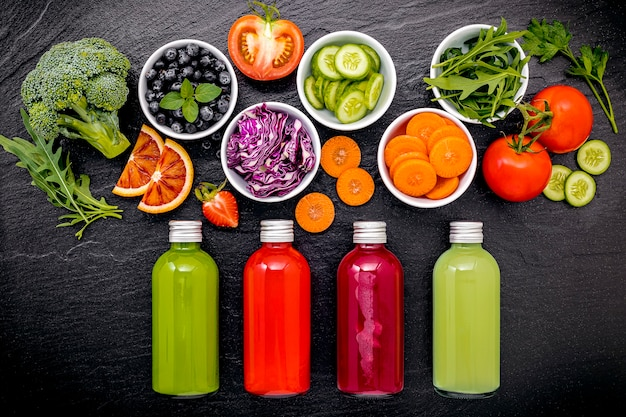 Colourful healthy smoothies and juices in bottles with fresh tropical fruit on dark stone background. Premium Photo