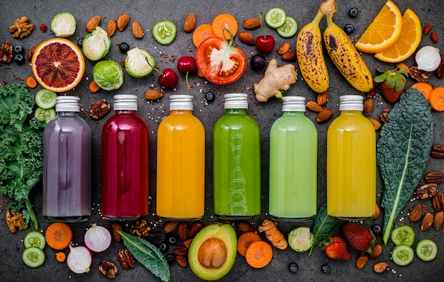 Colourful healthy smoothies and juices in bottles with fresh tropical fruit and superfoods on dark stone background with copy space. Premium Photo