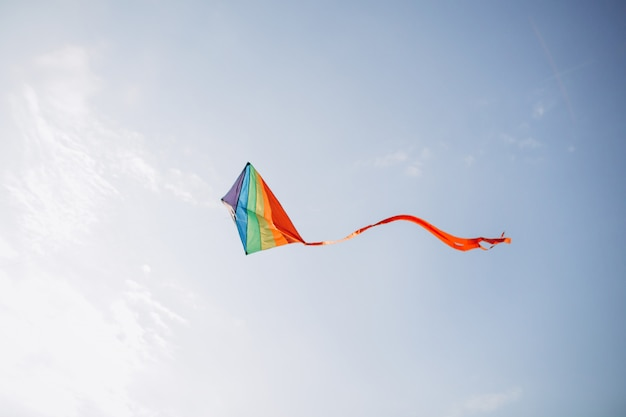 A colourful kite flying against a blue sky. Premium Photo