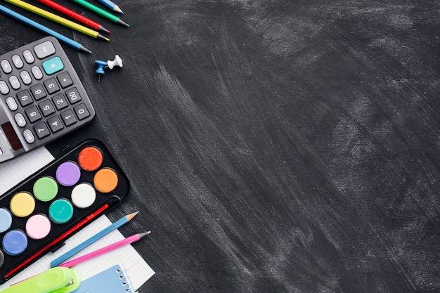 Colourful paints, calculator and pencils on grey background Free Photo
