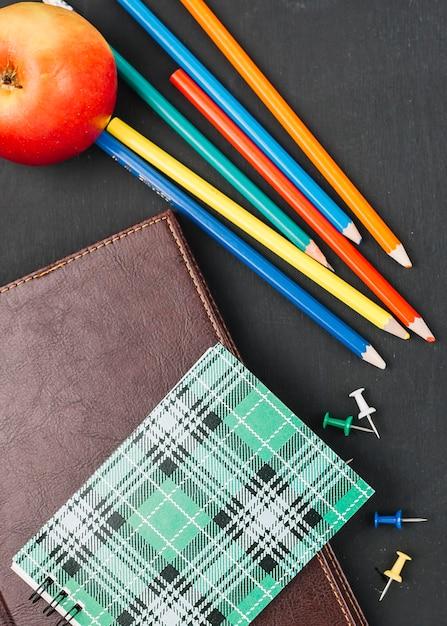 Colourful pencils among notebooks Free Photo
