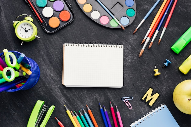 Colourful stationery, paints and clock surrounding notebook on grey background Free Photo