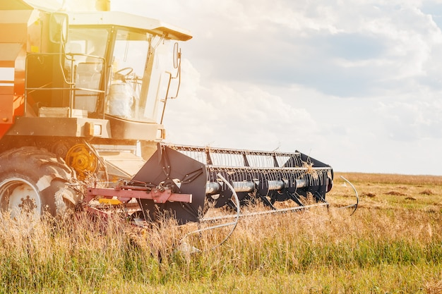 Combine harvester agriculture machine working in field close up Premium Photo