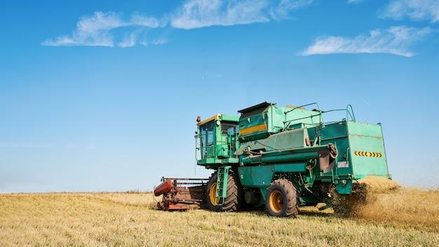 Зерноуборочный комбайн собирает спелую пшеницу. изображение сельского хозяйства Premium Фотографии