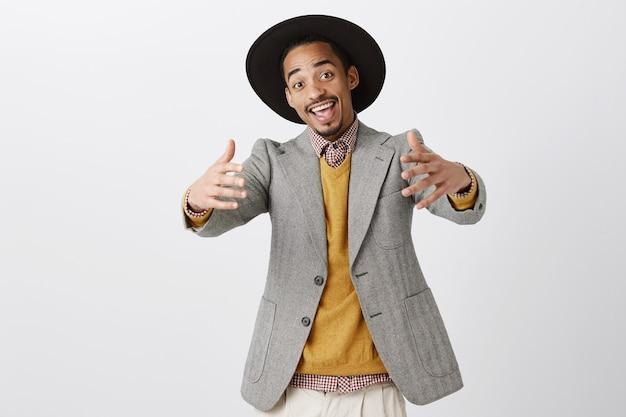 近くに来て、ハグさせて。トレンディな服装と帽子を引っ張る前向きなフレンドリーなアフリカ系アメリカ人 無料写真