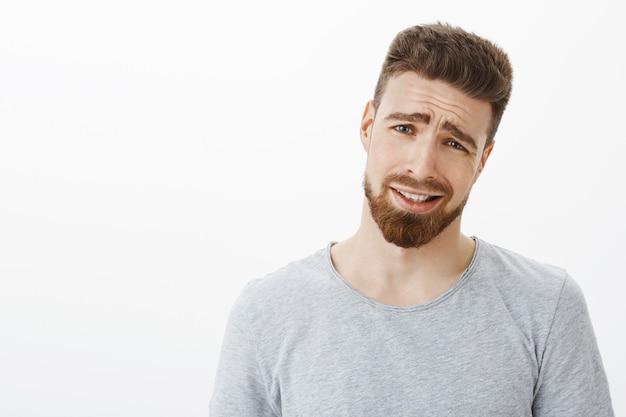 それはラメだ男に来る。ひげと青い目、頭を傾けて顔をしかめ、不満と不本意から目を細めて引き締める笑顔で不機嫌なハンサムなビジネスマン 無料写真