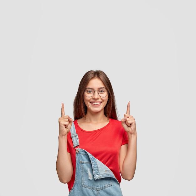 위층으로 올라와보세요. 행복한 감정적 인 백인 여자가 두 검지 손가락으로 위쪽을 가리 킵니다. 무료 사진