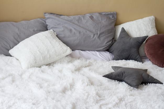 가벼운 침실, 가정의 편안함 개념, 복사 공간에 베개가있는 편안한 침대 프리미엄 사진