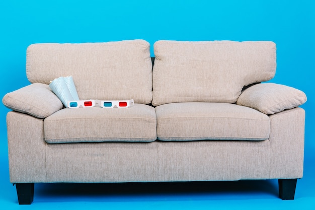 Comfortable couch with 3d glasses, popcorn isolated on blue background. preparing for watching movie, relaxation, enjoying cinema at home Free Photo