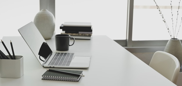 白い木製のテーブルにラップトップコンピューターとオフィス用品の快適な事務室 Premium写真