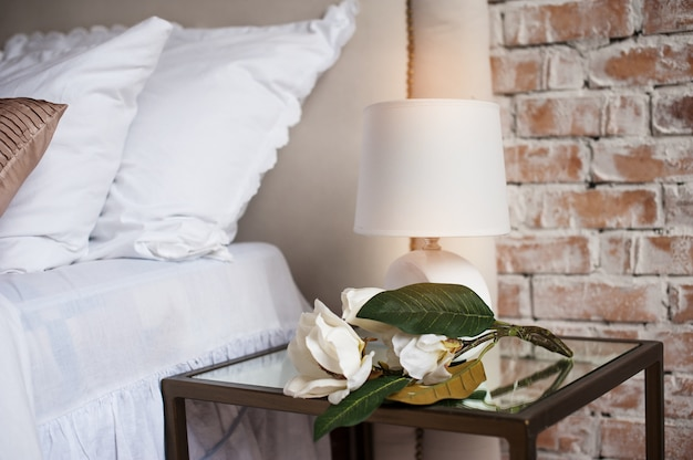 Comfortable and serene bedside with lamp by the bed Premium Photo