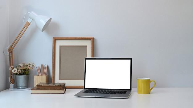 Удобное рабочее место с ноутбуком, ноутбуками, кофейной чашкой и деревом на белом столе. Premium Фотографии