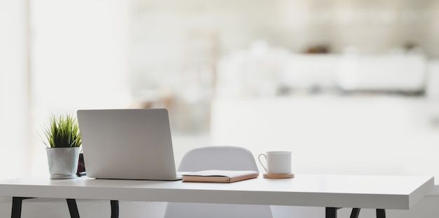 Comfortable workplace with laptop computer, coffee cup and office supplies Premium Photo