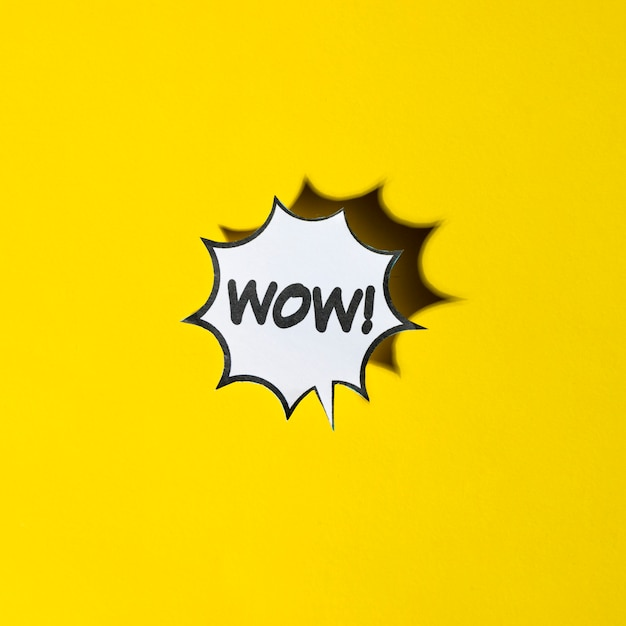 Comic cartoon speech bubble for wow emotions on yellow backdrop Free Photo
