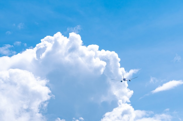 Commercial airline flying on blue sky and white fluffy clouds Premium Photo