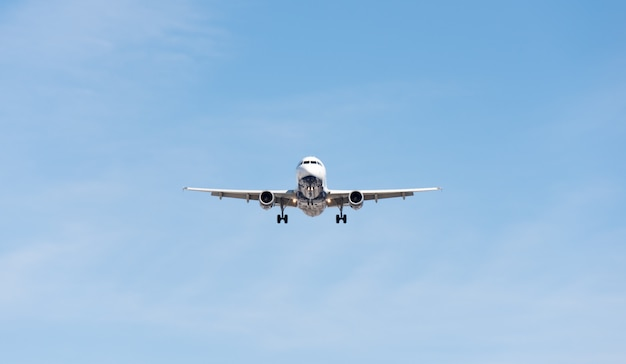Commercial airplane flying in blue sky, full flap and landing gear extended Premium Photo