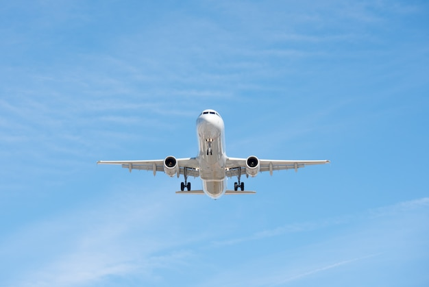 Commercial airplane flying in blue sky, full flap and landing gear extended