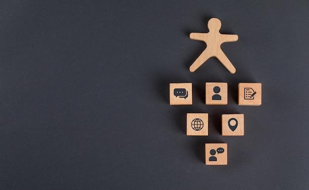 나무 조각에 아이콘으로 통신 개념, 어두운 회색 테이블 평면에 인간의 그림이하다. 무료 사진