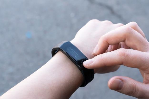 Концепция коммуникационных технологий крупным планом женщина настраивает умные часы перед тренировкой. Premium Фотографии