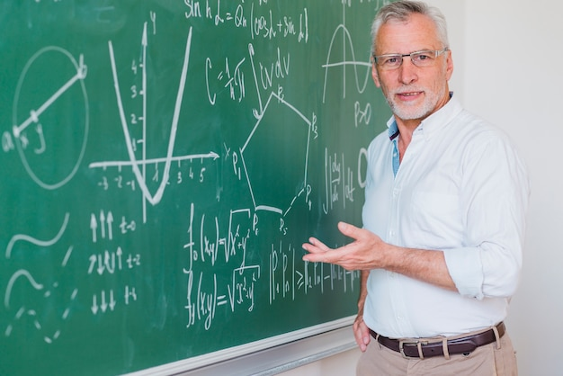 Communicative male lecturer standing at blackboard and pointing at equation Free Photo
