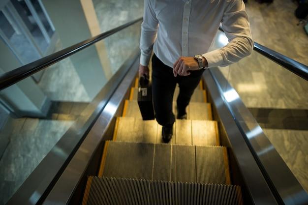 エスカレーターを歩きながら通勤者が時間をチェック 無料写真