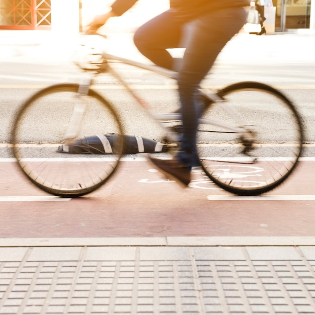 Commuter riding a bicycle on a city cycle lane Free Photo