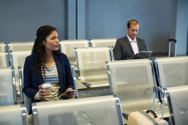 Пассажир, использующий мобильный телефон в зоне ожидания Бесплатные Фотографии