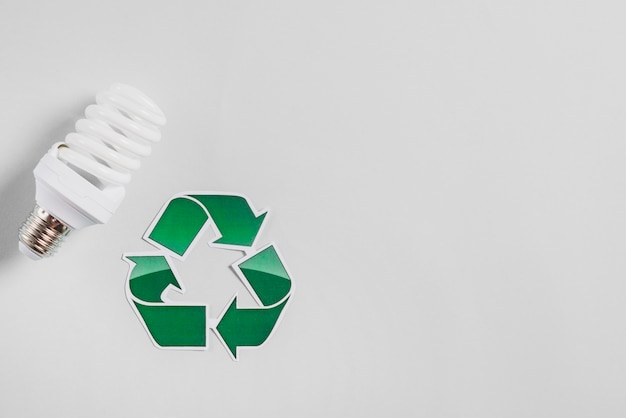 Compact fluorescent light bulb and recycle icon on white backdrop Free Photo
