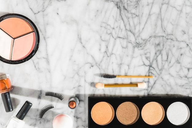 Compact powder; nail varnish; lipstick; eyelashes; mascara over marble textured backdrop Free Photo