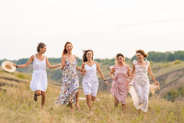 The company of cheerful female friends have a great time together on a picnic in a picturesque place overlooking the green hills. girls in white dresses dancing in the field Premium Photo